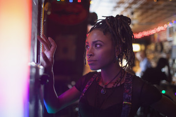 A young woman at a jukebox in a bar.