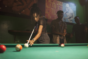 A young woman playing pool.