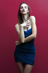 Fashion Model posing with a blue dress on a red wall