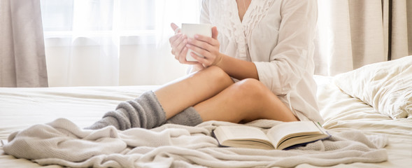 Young woman in bed while reading a book