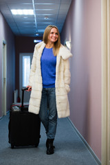 Positive adult woman standing in hall with packed luggage