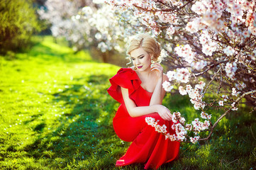 Portrait of a beautiful young blonde woman with long hair in red dress smiling on the background of pink cherry blossoms in spring