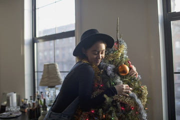 A young woman hugging a Christmas tree