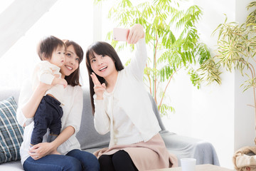 young asian family taking photo in living room