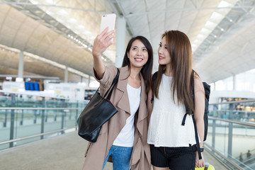 Friends taking selfie with mobile phone in airport