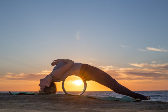 Blonde girl doing yoga on the beach. San Diego. California. Young woman with yoga wheel on sunset time