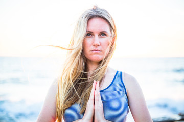 Blonde girl doing yoga on the beach at sunset time. Young woman in yoga pose with palms together. Open eyes