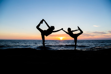 Two girls doing yoga on the beach at sunset time. San Diego. California. Yoga poses