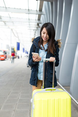 Woman go travel with her luggage and using mobile phone at Hong Kong international airport