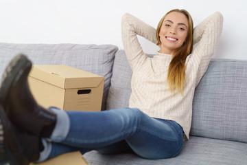 frau sitzt auf dem sofa mit mehreren kartons und legt entspannt die füße hoch