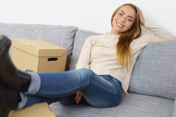 entspannte junge frau sitzt auf dem sofa und legt die füße auf umzugskartons