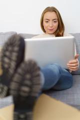 frau sitzt mit laptop auf dem sofa und legt die füße hoch