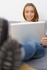 lachende junge frau mit laptop zu hause