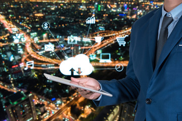 businessmen in blue suite using internet of things on mobile or tablet with night modern city background