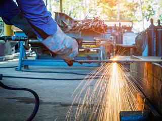 Worker cutting steel with acetylene welding cutting torch.
