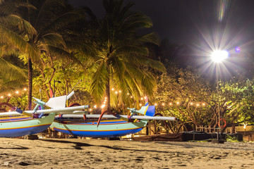 Fishing boats on the beach of tropical island Bali at night, Indonesia.