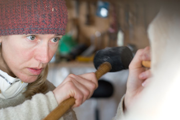 Woman carver chisels a sculpture