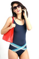 Portrait of girl in swiming suit with sun glasses and shooping bag speaking at smartphone