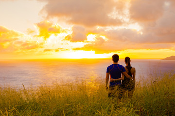 Couple standing in a field watching the sunset.