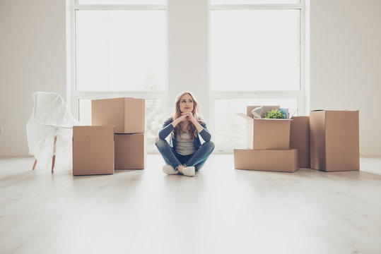 Dream come true! Portrait of young pretty woman sitting on the floor and thinking how to unpack all the stuff