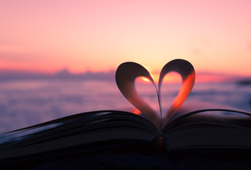 Heart from book against a beautiful sunset.