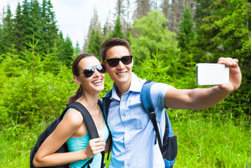 Young couple traveler taking self portrait in a beautiful forest setting.