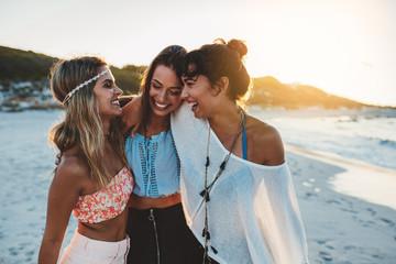 Stylish young women on beach at sunset