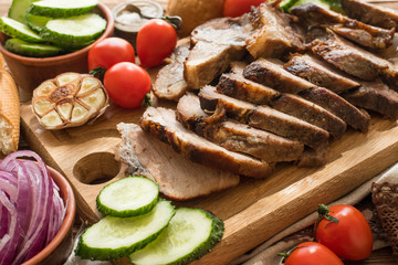 Sliced grilled meat barbecue on cutting board with vegetable .