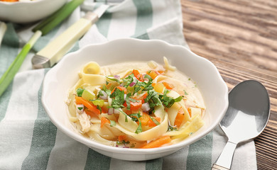 Chicken noodle soup in plate on table