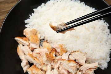 Black plate with delicious chicken and rice, closeup