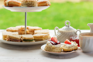 English afternoon teas in the garden cafe: scones with clotted cream and jam, strawberries, with various sadwiches on the background, selective focus