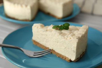 Piece of delicious cheesecake on blue plate