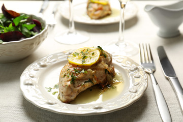 Plate with delicious chicken breast on served table