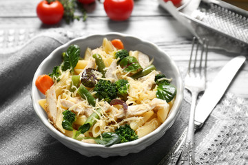 Bowl with tasty chicken and noodles on table