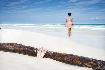 Girl with flip flops walking at beach in Mexico / Beauty walking over Driftwood