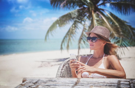 Young beautiful woman with mobile phone on the shore of the tropical sea in a cafe. Communication and internet in travel concept