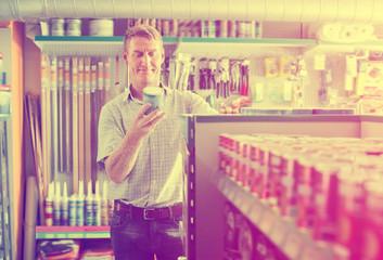 Man customer picking paint tin