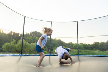 Children jumping on a trampoline in a park without parental supervision