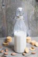 Nutritional almond nut milk in glass bottle on rustic vintage wooden table. Vegan dairy free healthy calcium.