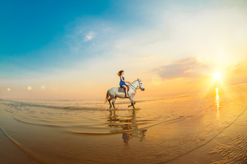 Woman and horse on the background of sky and water. Girl model on horseback on the beach by the sea at sunset, backlit in sunshine. A positive summer time scene.
