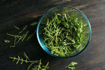 Mix of fresh green arugula in a glass bowl placed on a black table top made of a textured wooden board.