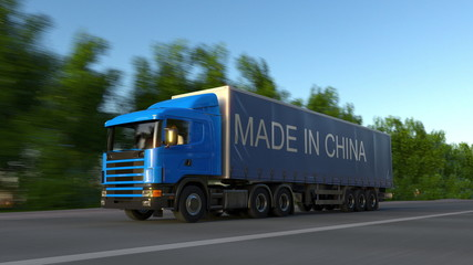 Speeding freight semi truck with MADE IN CHINA caption on the trailer. Road cargo transportation. 3D rendering