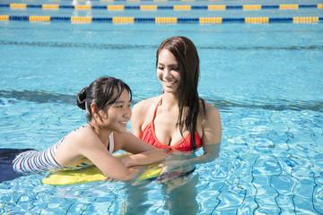 Beautiful young mother teaching girl swimming.