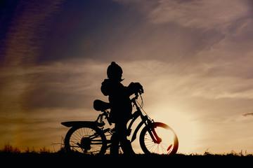 little boy riding bike at sunset sky