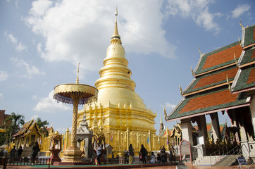 Asian thai people and foriegner people respect praying and walk visit gold chedi at Wat Phra That Hariphunchai