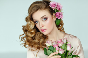 Portrait of a beautiful blonde girl with delicate pink roses on a light background in the studio. Close-up