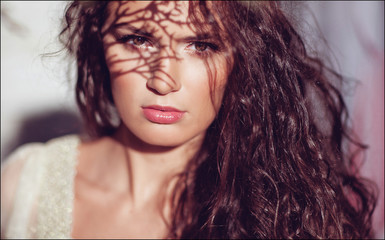 Sensual beautiful curly girl with a shadow from a branch on the face, close up