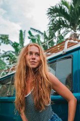 Red hair surf girl near blue vintage mini van with palm trees in the background in grey swimsuit, Indonesia, Bali