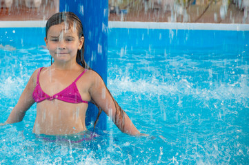 Little girl in the pool bathe, happy, splash