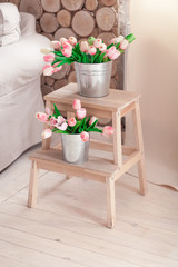 Beautiful gentle tulips in a bucket on a wooden stand for flowers near the sofa